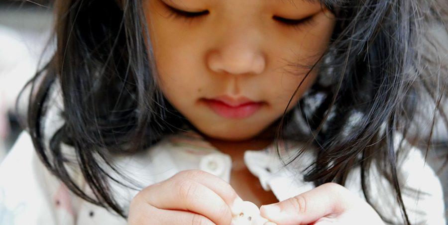 petite fille qui met un bouton